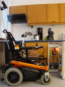 The autonomous wheelchair being demonstrated for the Technology Foundation in Berlin. The wheelchair can also be retrofitted with a robotic arm for reaching objects (right).